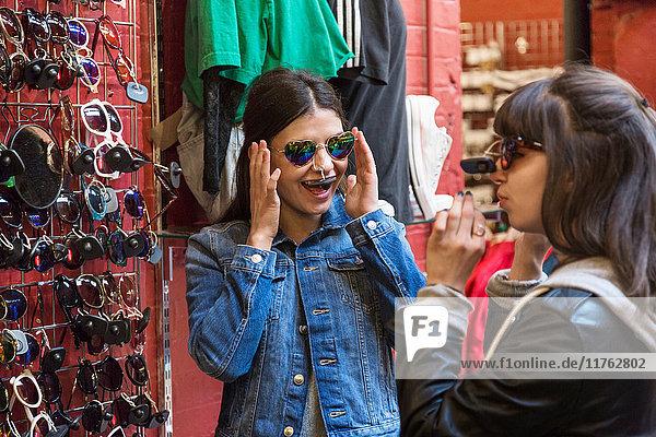 Junge Käuferinnen probieren in der Markthalle eine Sonnenbrille an