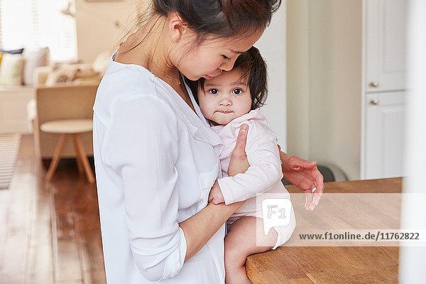Frau umarmt Baby-Tochter auf Küchentheke