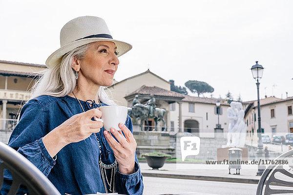 Reife Frau trinkt Kaffee im Strassencafé  Fiesole  Toskana  Italien