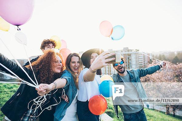 Gruppe von Freunden genießt Dachparty  hält Heliumballons in der Hand  junge Frau nimmt Selfie mit Smartphone