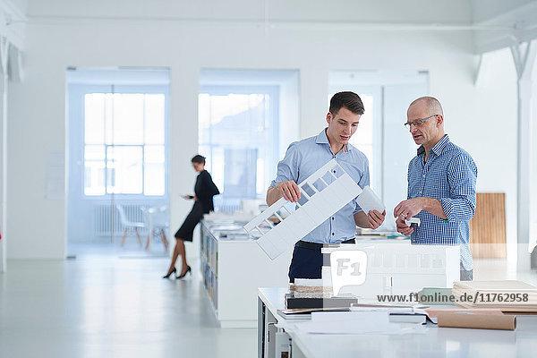 Amtierende Architekten betrachten Architekturmodell