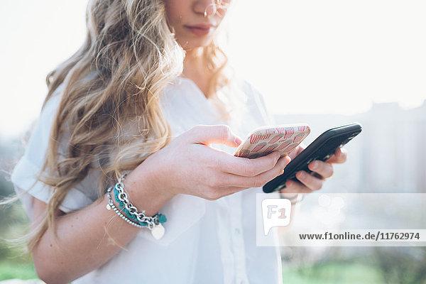 Junge Frau im Freien  schaut auf zwei Smartphones  mittlerer Abschnitt