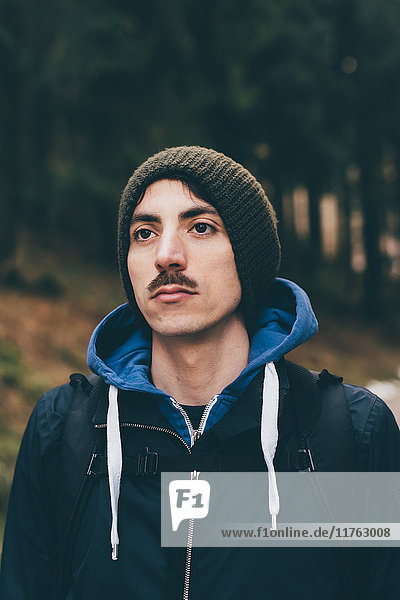 Portrait of male hiker wearing knit hat in forest  Monte San Primo  Italy