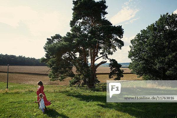 Schwangere Frau und Kleinkind-Tochter spazieren in Feldlandschaft