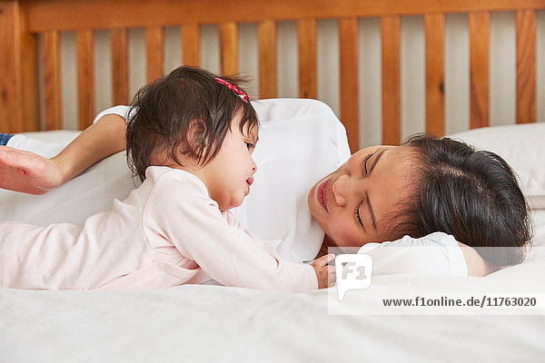 Woman reclining on bed with baby daughter