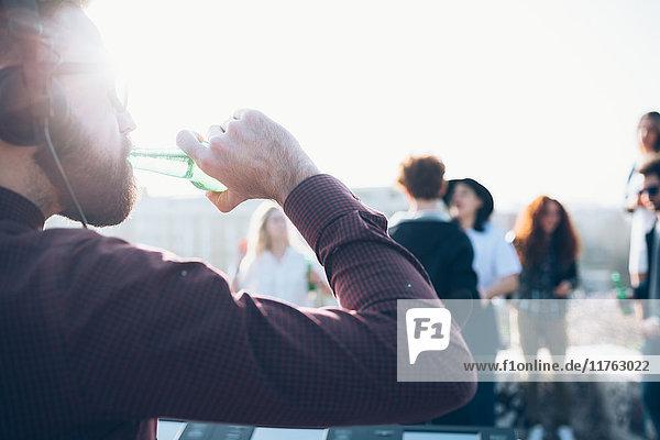 Gruppe von Freunden genießt Dachparty  junger Mann trinkt aus Bierflasche