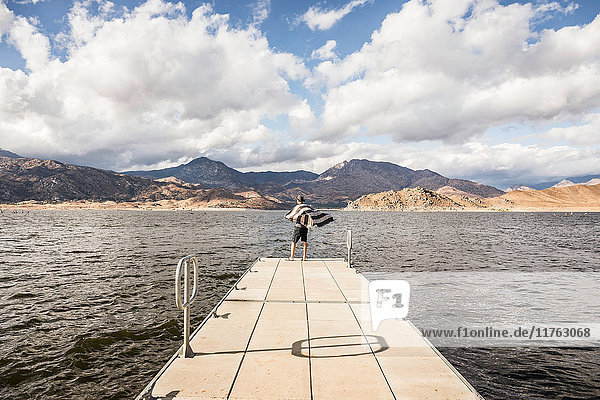 Rear view of man looking out from windy pier on Lake Isabella  California  USA