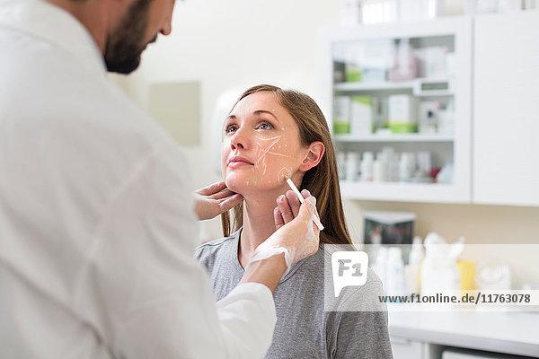 Kosmetischer Chirurg  der das Gesicht des Patienten für die Operation markiert