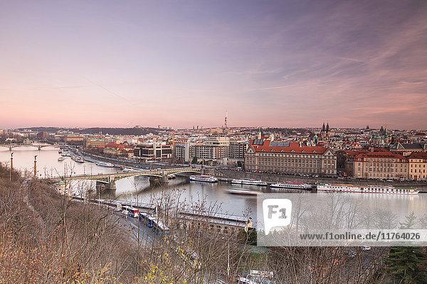Pink sky on historical bridges and buildings reflected on Vltava River at sunset  Prague  Czech Republic  Europe