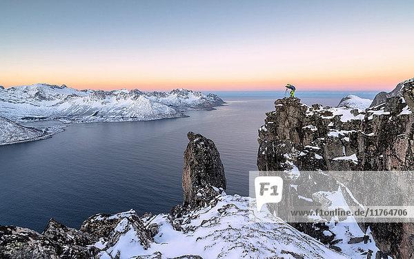 Photographer on the rocks on top of Mount Hesten admires the Mefjorden and the frozen sea at sunrise  Senja  Troms  Norway  Scandinavia  Europe