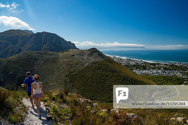 Man and woman hikers walking down into Hermanus from the mountain  Hermanus  South Africa  Africa