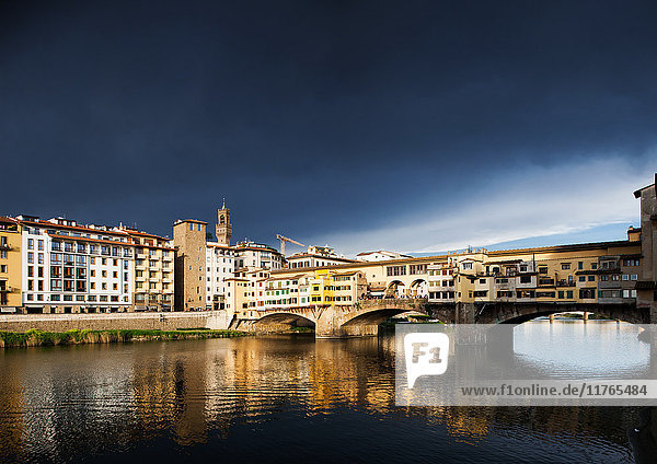 Ponte Vecchio reflecting in the Arno rRver against a dark blue stormy sky  Florence  UNESCO World Heritage Site  Tuscany  Italy  Europe