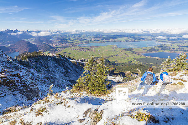 Hikers on steep crest covered with snow in the Ammergau Alps  Tegelberg  Fussen  Bavaria  Germany  Europe