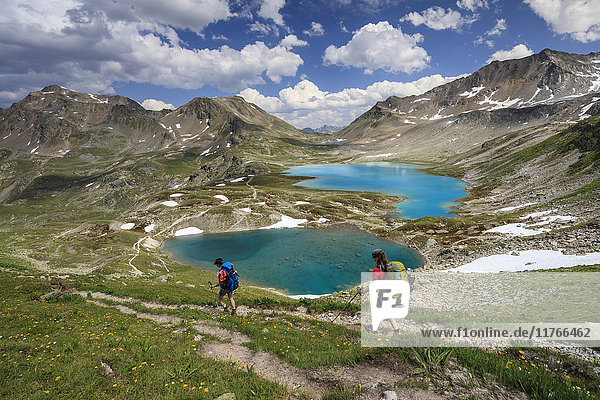 Hikers pass the turquoise lake and rocky peaks  Joriseen  Jorifless Pass  canton of Graubunden  Engadine  Switzerland  Europe