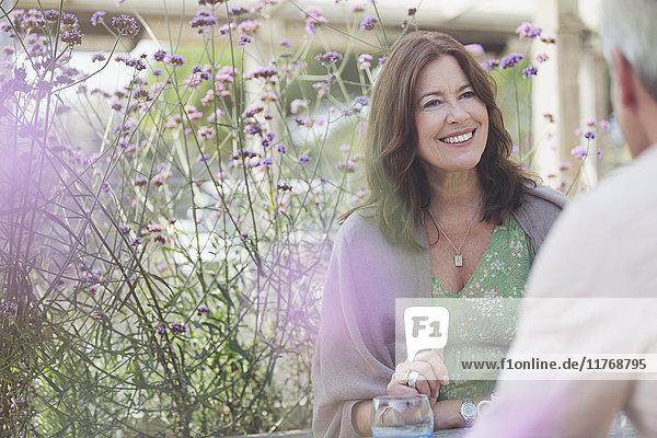 Lächelndes reifes Paar auf der Terrasse mit violetten Blumen