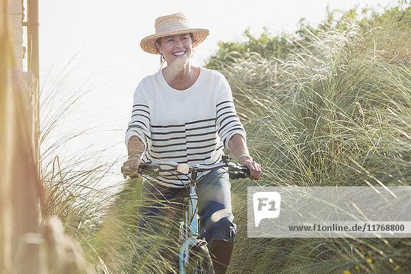 Lächelnde reife Frau beim Fahrradfahren entlang des Strandgrases