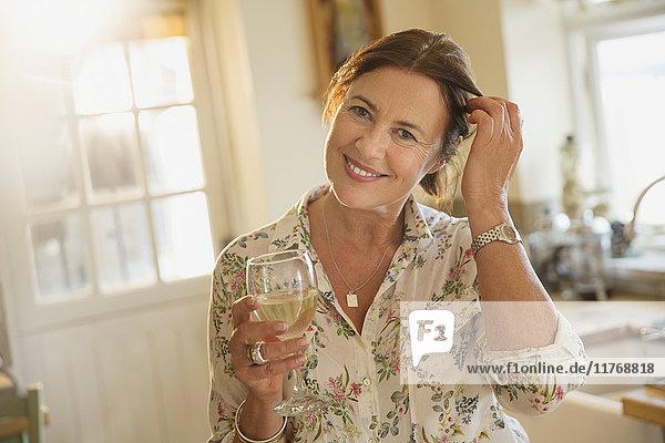 Portrait lächelnde reife Frau trinkt Weißwein in der Küche