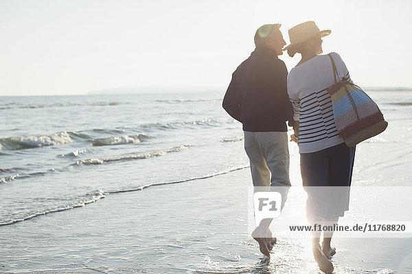 Barfuss reifes Paar  das am Strand bei Sonnenuntergang spazieren geht.