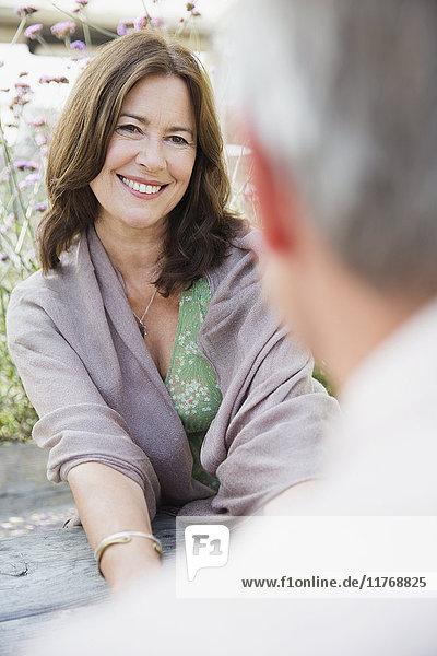 Reife Frau lächelt den Mann an.
