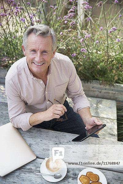 Portrait lächelnder älterer Mann mit digitaler Tablette und Kaffeetrinken am Terrassentisch