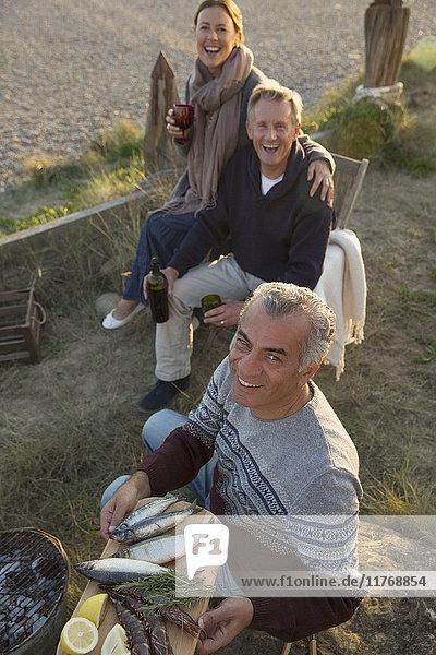 Portrait lächelnde reife Freunde beim Grillen und Weintrinken am Strand