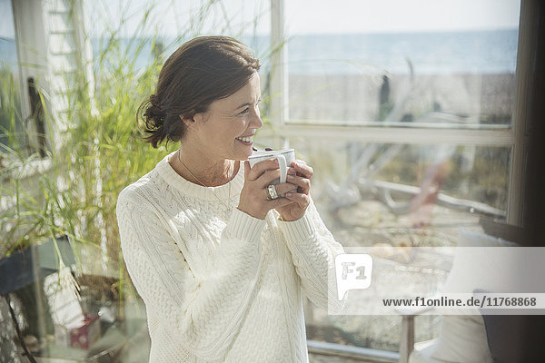 Smiling mature woman drinking coffee on beach house sun porch