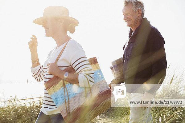 Reife Paare beim Spaziergang im sonnigen Strandgras