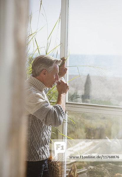 Senior Mann trinkt Kaffee am sonnigen Strandhausfenster