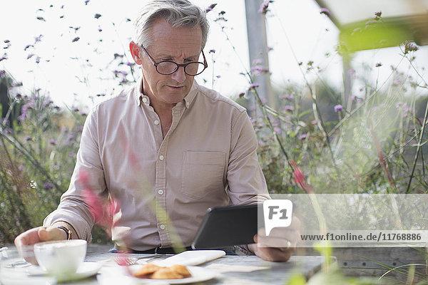 Senior Mann mit digitaler Tablette und Kaffee trinken auf der Terrasse Tisch