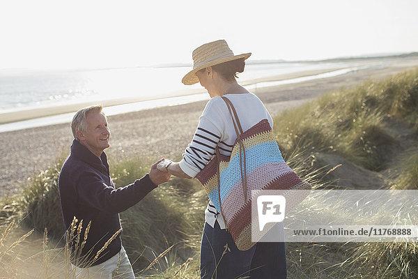 Ehemann hilft Frau auf sonnigem Strandgrasweg