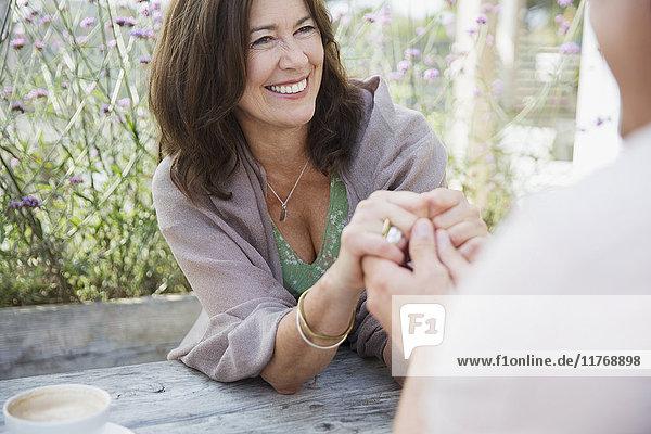Zärtliches  reifes Paar  das sich an einem Terrassentisch an den Händen hält.