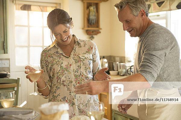 Verspieltes reifes Paar beim Backen in der Küche