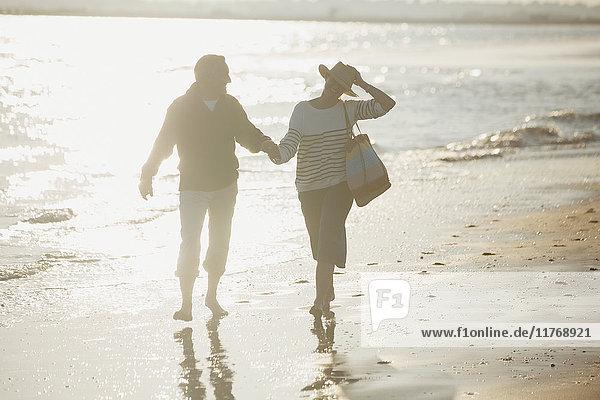 Ein reifes Paar hält sich an den Händen und geht am sonnigen Strand spazieren.