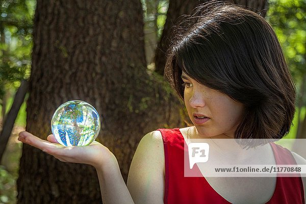 Young woman  standing by a tree in a park  holding a crystal ball.