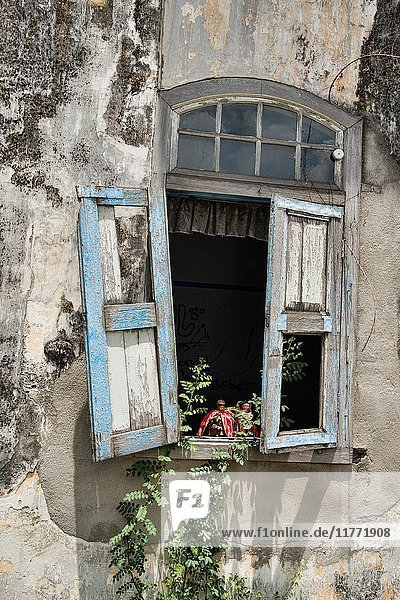 Small statues in dilapidated house  Malacca  Malaysia.