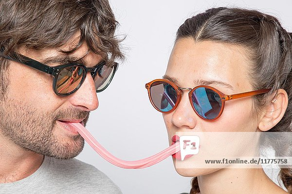 Mid-adult couple wearing sunglasses  sharing candy