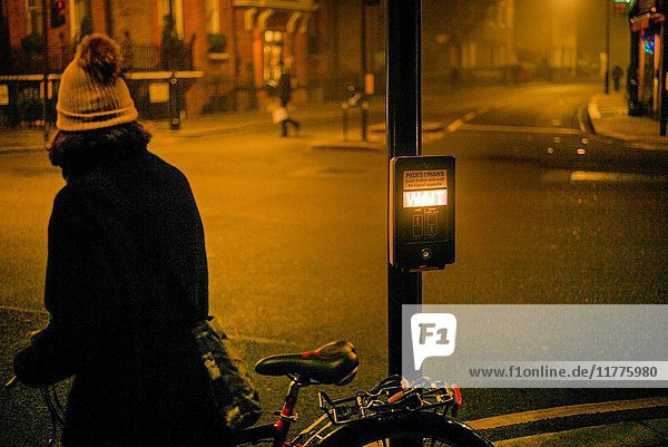 Unrecognizable woman on bicycle waiting at pedestrian crossing. London  England