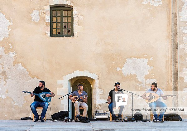 Traditional Greek group performing behind the Mosque of the Janissaries  Chania  Crete  Greece.