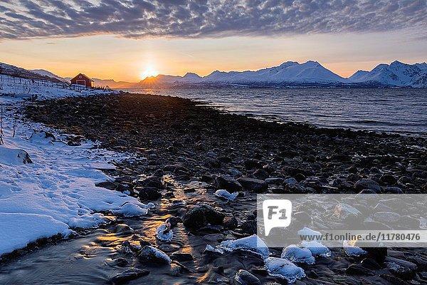 The sun sets behind the Lyngen Alps. Nordmannvik  Kafjord  Lyngen Alps  Troms  Norway  Lapland  Europe.