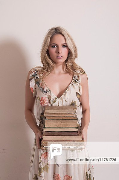 Young woman holding a pile of old books.