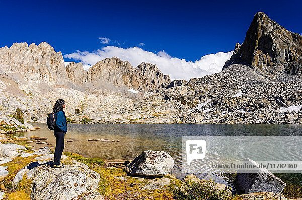 Hiker under Isosceles Peak and the Palisades in Dusy Basin,  Kings Canyon National Park,  California USA.