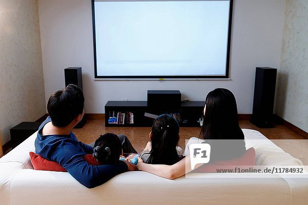 Happy family watching TV in sofa back view