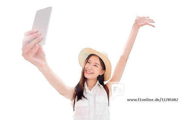 Young woman taking self-portrait with smart phone