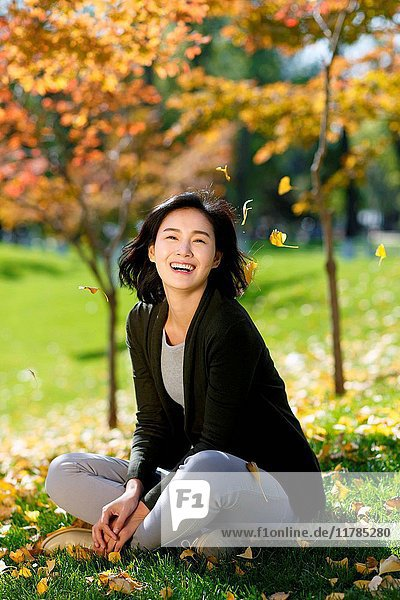 Young woman sitting on fallen leaves in grass