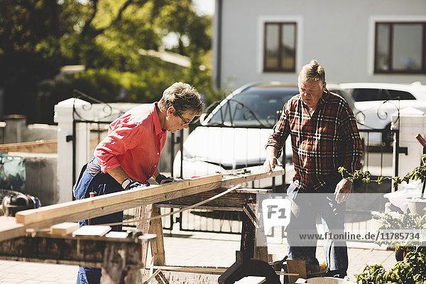 Seniorenpaar beim Vermessen von Holzbrettern auf dem Hof