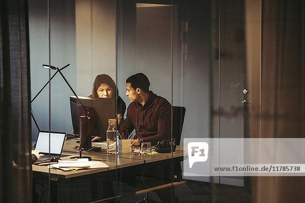 Geschäftsleute diskutieren bei der Arbeit am Schreibtisch im dunklen Büro
