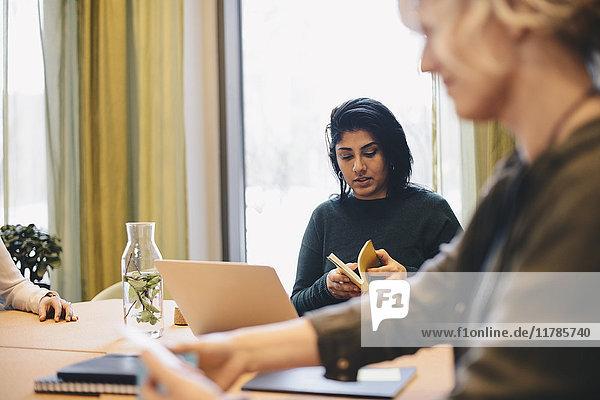 Geschäftsfrau beim Sitzen mit Kollegin am Schreibtisch im Sitzungszimmer