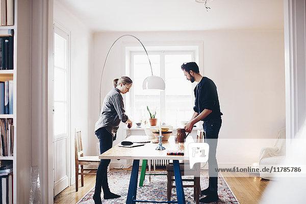 Seitenansicht des Paares  das Objekte auf dem Esstisch zu Hause anordnet.