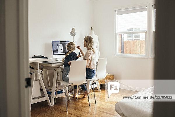 Rückansicht des Design-Profis mit Tochter am Computer zu Hause