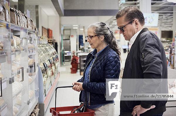 Ein reifes Paar schaut sich im Supermarkt den Lebensmittelschrank an
